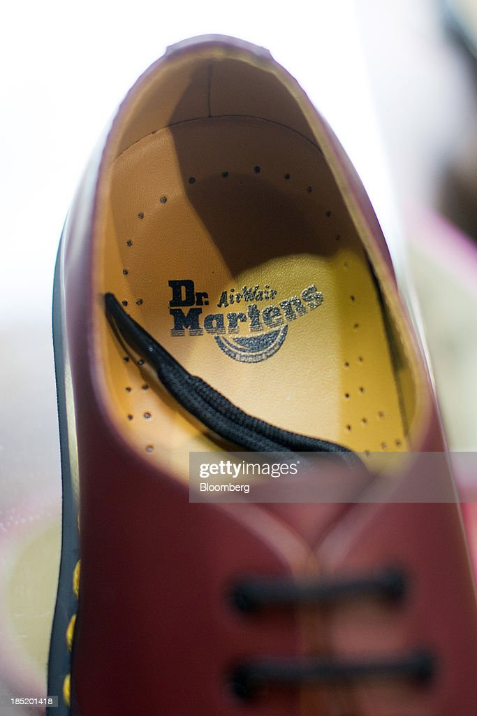 An 'AirWair' logo sits on the insole of a Dr. Martens shoe displayed for sale inside a footwear store in London, U.K., on Friday, Oct. 18, 2013. Permira Advisers LLP, the London-based private-equity firm that owns clothing brand Hugo Boss, is in advanced talks to buy iconic British punk-boot maker Dr. Martens, said a person with knowledge of the negotiations. Photographer: Simon Dawson/Bloomberg via Getty Images