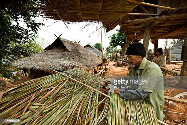 An Akha man works on preparing roofing thatch for traditional Akha houses in Pae Sangsun village