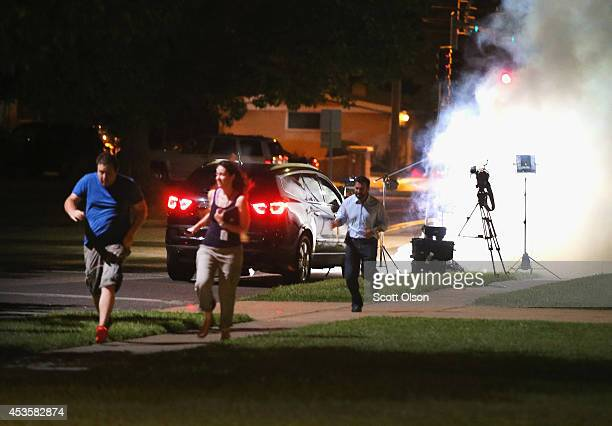 An Al Jazeera television crew covering demonstrators protesting the shooting death of teenager Michael Brown scramble for cover as police fire tear...