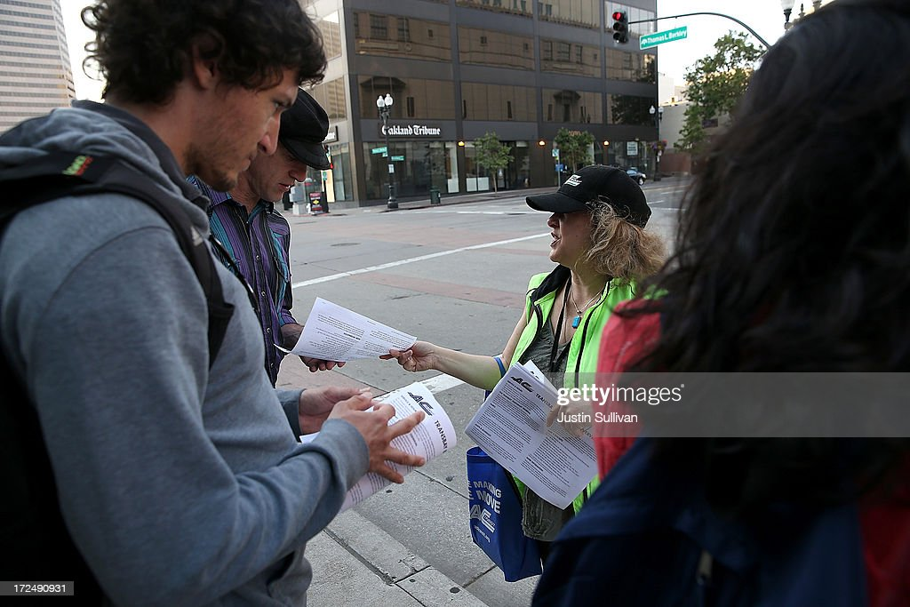 An Alameda-Contra Costa (AC) Transit worker passes out bus information to commuters as they wait in line to board an AC Transit bus on July 2, 2013 in Oakland, California. For a second day, hundreds of thousands of San Francisco Bay Area commuters are scrambling to find ways to work after two of San Francisco Bay Area Rapid Transit's (BART) largest unions went on strike early yesterday morning following contract negotiations with management falling apart the day before. Train operators, mechanics, station agents and maintenance workers are seeking a five percent wage increase and are fighting management who want to have workers to begin contributing to their pensions, pay more for health insurance and reduce overtime expenses.