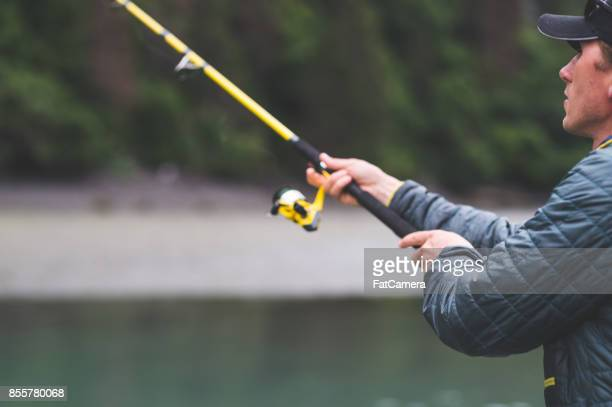 An Alaska fisherman holds his rod out over the water.