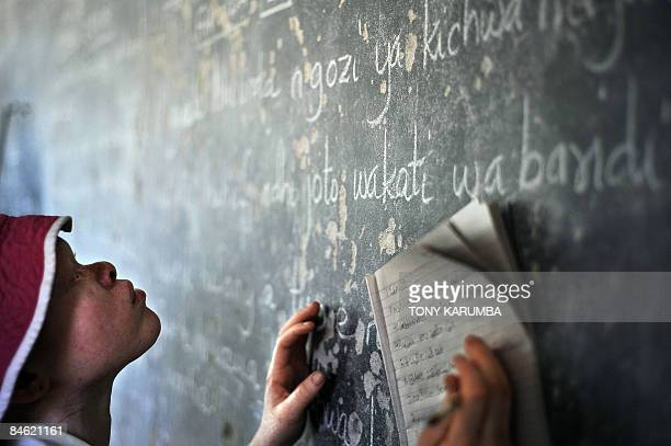 An Albino teenage girl copies on January 28 2009 notes off a blackboard in her classroom at the Mitindo Primary School for the blind which has become...