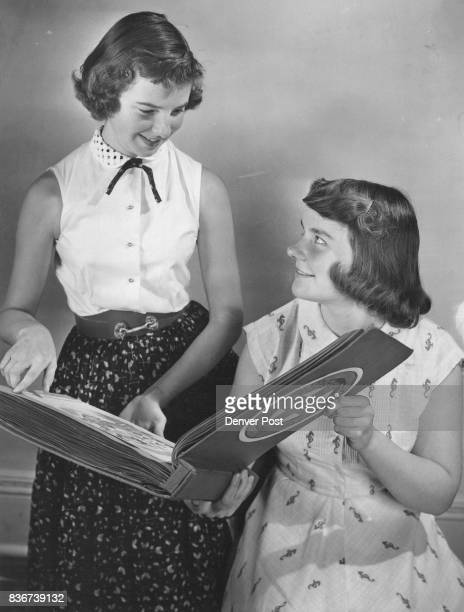 An album made up by Junior Red Cross members of Salonika Greece is admired/by Nancy Meredith of 1061 Detroit St and Kay Brainerd of 848 Washington St...