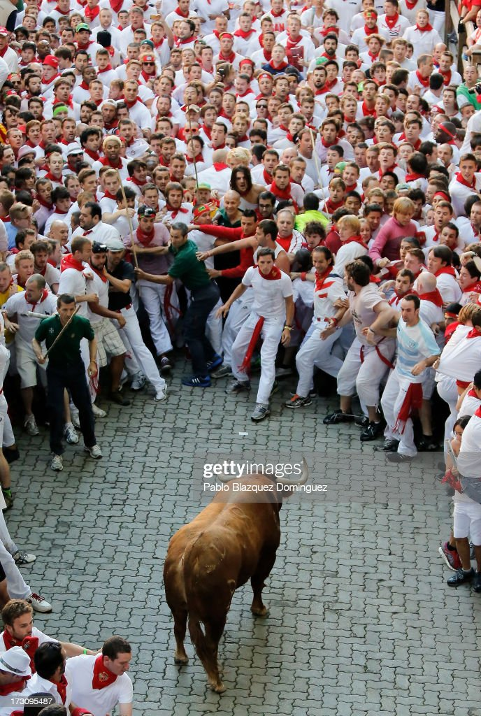 An Alcurrucen's ranch fighting bull stands alone surrounded by a crowd of runners on the way to entering the bullring during the second day of the San Fermin Running Of The Bulls festival, on July 7, 2013 in Pamplona, Spain. The annual Fiesta de San Fermin, made famous by the 1926 novel of US writer Ernest Hemmingway 'The Sun Also Rises', involves the running of the bulls through the historic heart of Pamplona, this year for nine days from July 6-14.