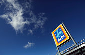 An Aldi logo sits on a sign above the entrance to an Aldi discount supermarket operated by Aldi Stores Ltd in Chelmsford UK on Tuesday Oct 7 2014 Wm...