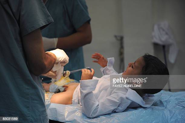 An Algerian boy screams before being circumcised during a mass circumcision at a local hospital September 27 2008 in Algiers The Muslim religion...