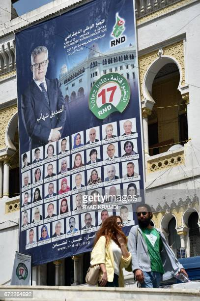 An Algerian couple walk past an election campaign poster of the Rassemblement National Democratique party outside its bureau in the capital Algiers...
