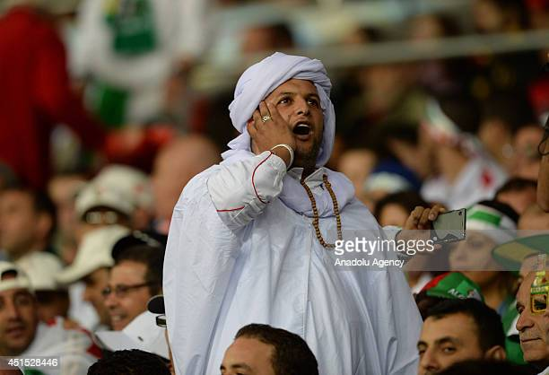 An Algerian Muslim soccer fan recites the azan at the time to break fast during the 2014 FIFA World Cup Brazil Round of 16 match between Germany and...