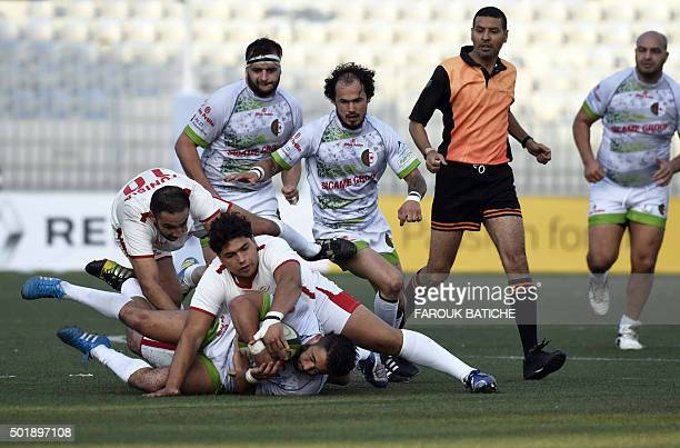 An Algerian player is tackled by Tunisian players during their friendly rugby match Alegria's first international rugby match on home soil on...
