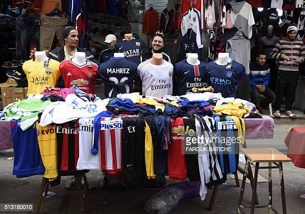 An Algerian vendor displays shirts of football players at a market on February 18 2016 in the old part of the capital Algiers known as the Casbah...