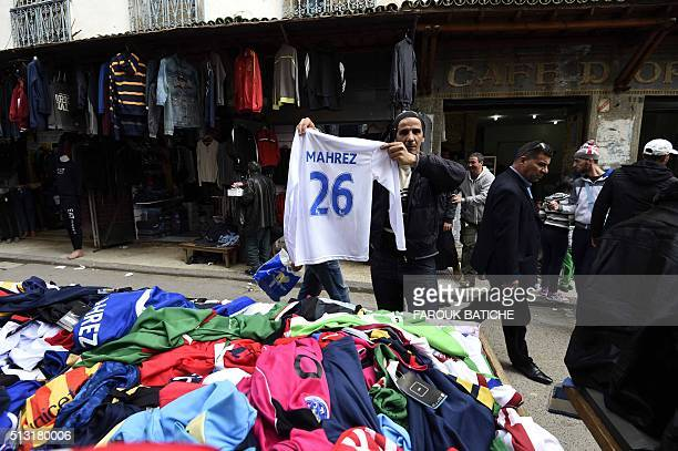 An Algerian vendor shows a shirt of English football club Leicester City's midfielder Riyad Mahrez on February 18 2016 at a market in the old part of...
