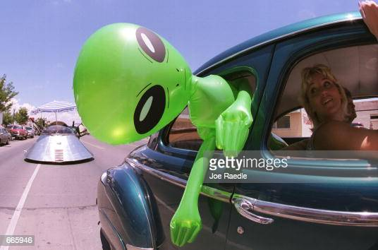 An alien doll hangs out a car window in downtown Roswell New Mexico July 1 2000 as part of the annual UFO Encounter which runs through July 4 2000...
