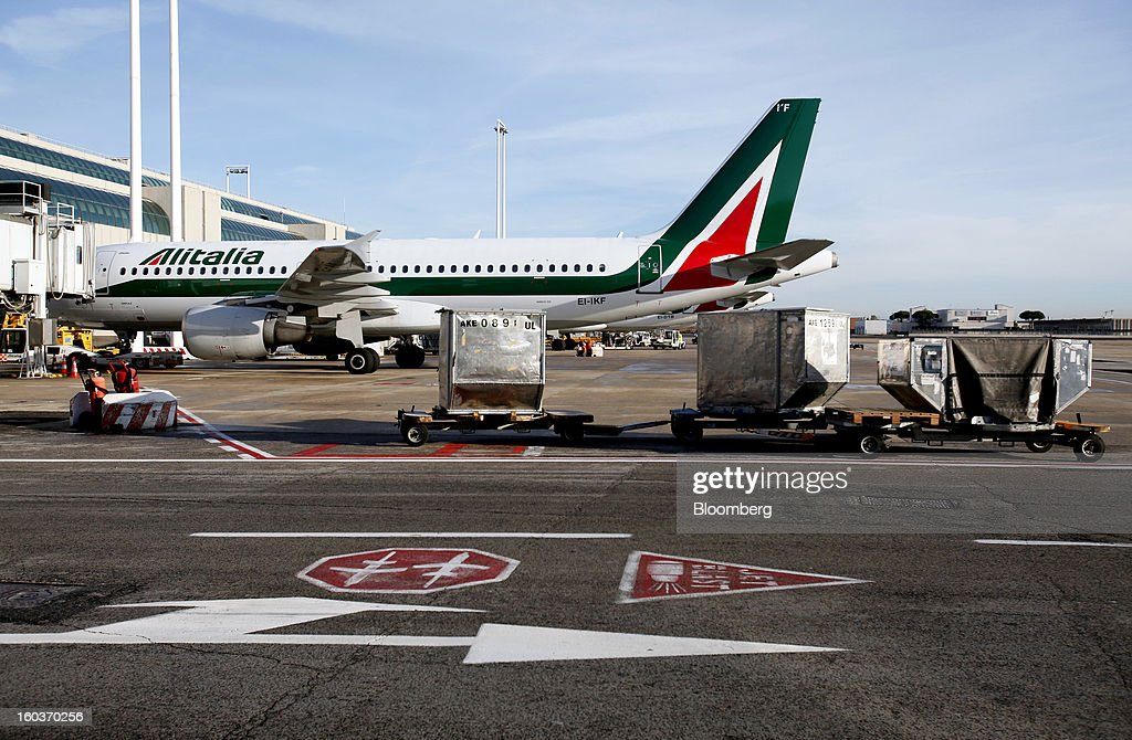An Alitalia SpA aircraft stands at a terminal gate at Fiumicino airport in Rome, Italy, on Tuesday, Jan. 29, 2013. Italian business confidence unexpectedly fell to the lowest since October as the country's fourth recession since 2001 deepened, damping the outlook for an economic recovery. Photographer: Alessia Pierdomenico/Bloomberg via Getty Images