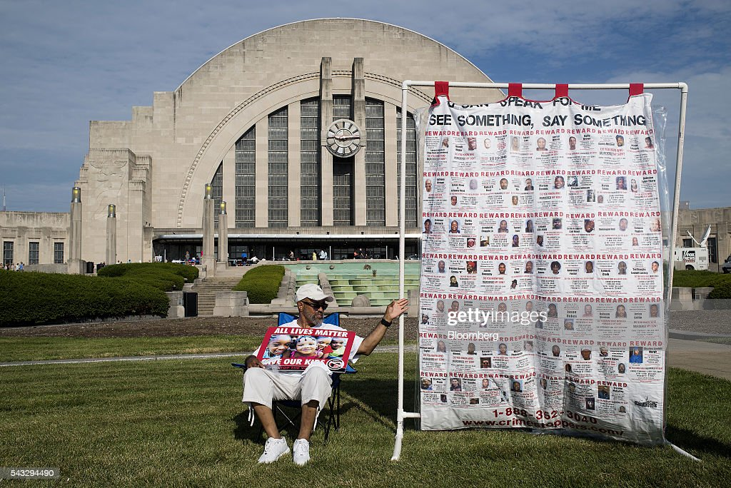 An 'All Lives Matter' supporter sits in front of the Cincinnati Museum Center at Union Terminal ahead of a campaign event with Hillary Clinton, former Secretary of State and presumptive Democratic presidential nominee, not pictured, in Cincinnati, Ohio, U.S., on Monday, June 27, 2016. Clinton released a new national television ad on Sunday attacking likely Republican rival Donald Trump for his comments on the U.K's decision to leave the European Union, and later warned of the negative impact that 'bombastic' behavior can have at times of crisis. Photographer: Ty Wright/Bloomberg via Getty Images