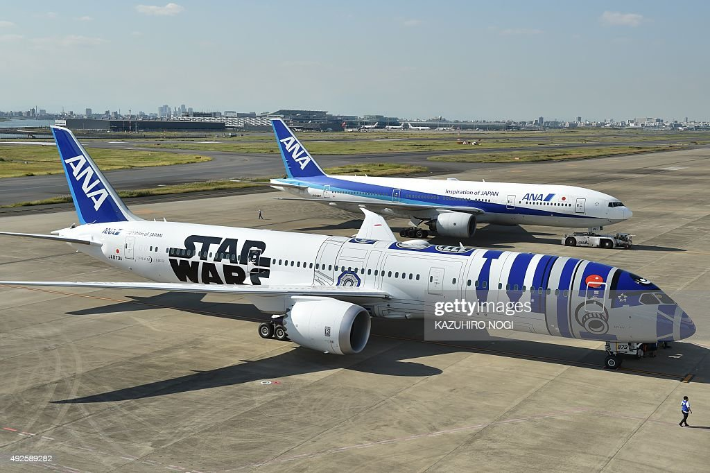 An All Nippon Airways (ANA) Boeing 787-9 aircraft in the livery of Star Wars droid character R2-D2 (front) is seen on the tarmac at Tokyo's Haneda airport on October 14, 2015, as part of the company's Star Wars project. The Boeing aircraft is scheduled to go into service on international routes after a fan appreciation flight event on October 17. / AFP / KAZUHIRO
