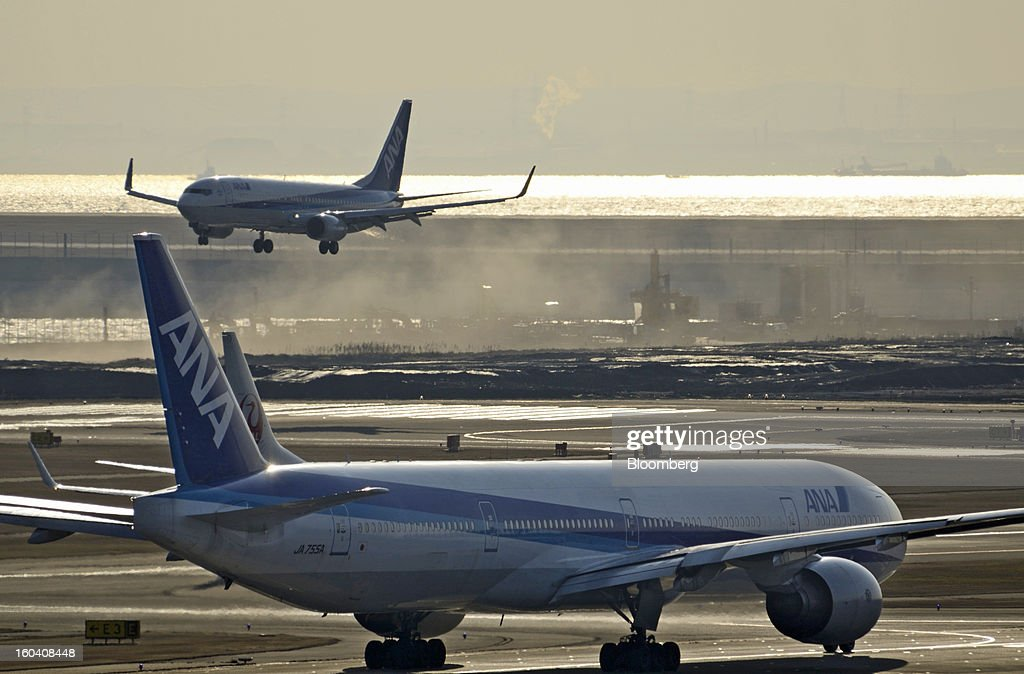 An All Nippon Airways Co. (ANA) aircraft, front, prepares to take off as another lands at Haneda Airport in Tokyo, Japan, on Wednesday, Jan. 30, 2013. ANA has canceled a total of 784 flights, affecting 74,200 passengers through Feb. 12, since a Jan. 16 incident that led to the global grounding of Boeing Co. 787s, according to figures from the company. Photographer: Akio Kon/Bloomberg via Getty Images