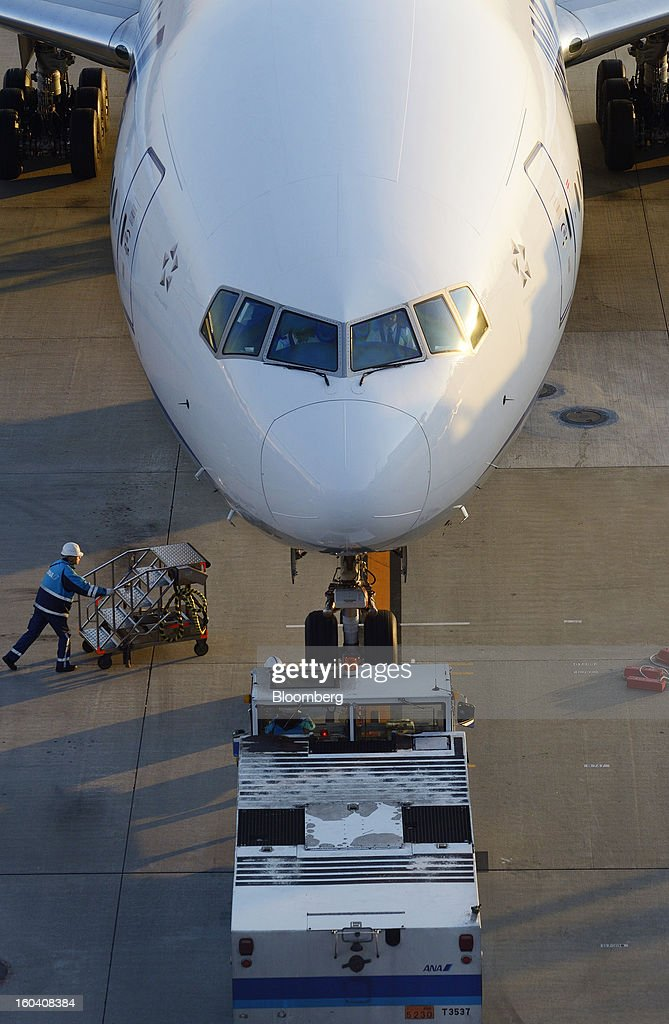 An All Nippon Airways Co. (ANA) aircraft is pushed back by a tug as a member of the ground staff approaches with a step ladder at Haneda Airport in Tokyo, Japan, on Wednesday, Jan. 30, 2013. ANA has canceled a total of 784 flights, affecting 74,200 passengers through Feb. 12, since a Jan. 16 incident that led to the global grounding of Boeing Co. 787s, according to figures from the company. Photographer: Akio Kon/Bloomberg via Getty Images