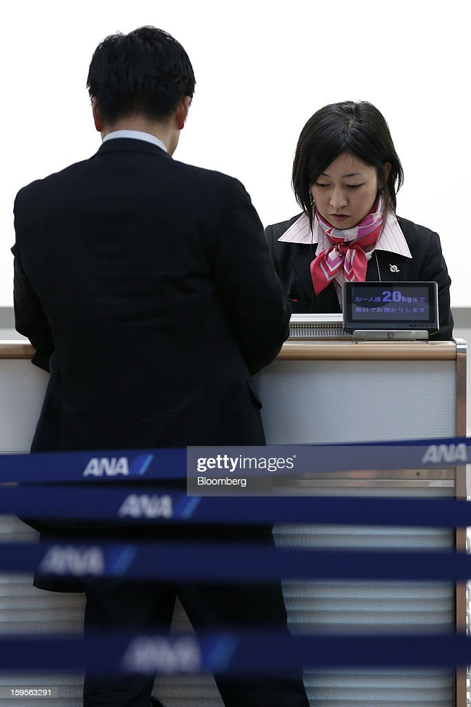 An All Nippon Airways Co. (ANA) employee assist a passenger with his flight cancellation at Haneda Airport in Tokyo, Japan, on Wednesday, Jan. 16, 2013. ANA and Japan Airlines Co. (JAL), the world's largest users of Boeing Co. 787 jets, grounded their entire fleet of Dreamliners for today in the biggest blow yet to the troubled passenger jet's image. Photographer: Kiyoshi Ota/Bloomberg via Getty Images
