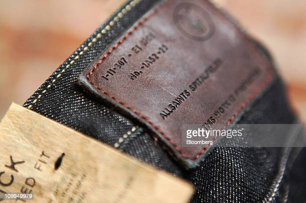 An All Saints Retail Ltd label is displayed on a pair of jeans at the company's store in London UK on Friday March 11 2011 Retailers are under...