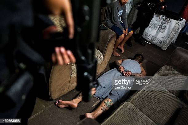 An alleged gang member lies on the floor handcuffed by the special antigang unit during a night raid in Soyapango a gang neighborhood on December 12...