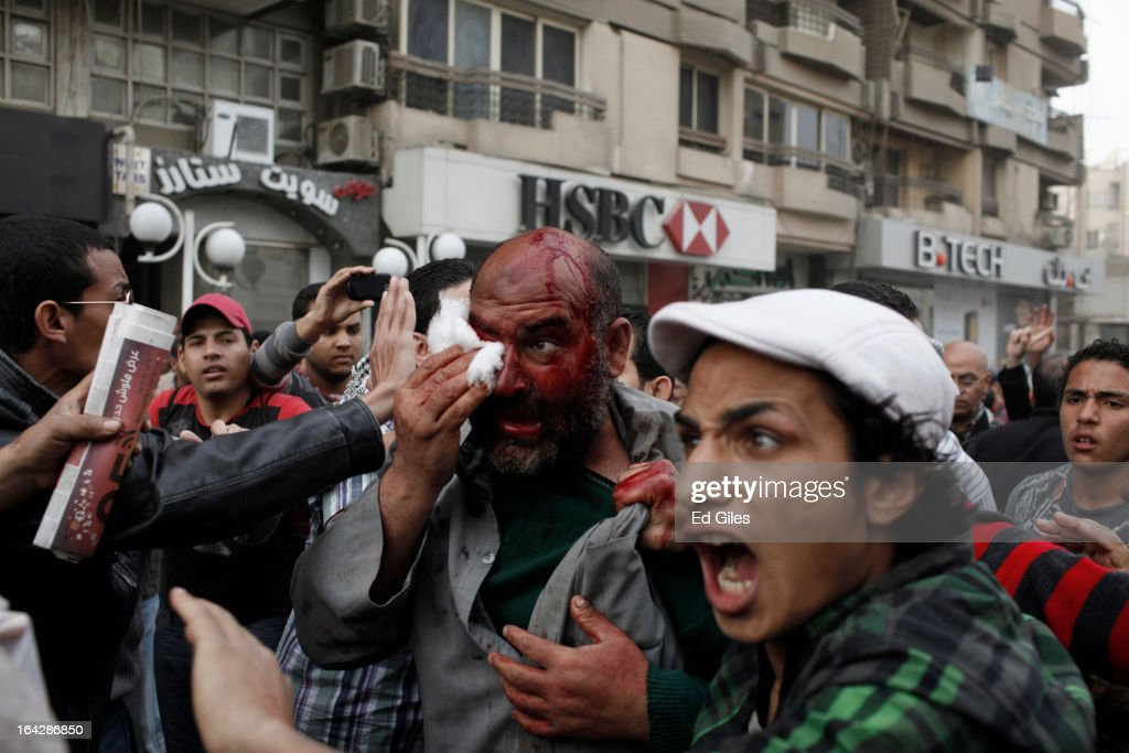 An alleged member of the Muslim Brotherhood is dragged through a crowd of protesters after being beaten on the head during clashes between opposition demonstrators and supporters of the Muslim Brotherhood on March 22, 2013 in Cairo, Egypt. Opposition demonstrators converged on the headquarters of the Muslim Brotherhood in the Cairo suburb of Muqattam to protest against the government of President Mohammed Morsi, who is closely connected to the Muslim Brotherhood movement. (Photo by Ed Giles/Getty Images).