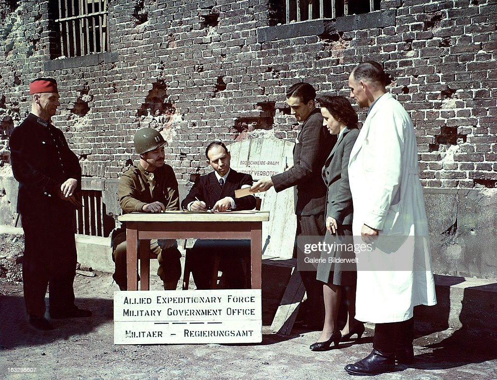 An Allied Expeditionary Force Military Government Office has been set up. July 1945. An US Public Safety Officer wearing a helmet & Mr. Jacoby (seated), director of Cologne prison, are interviewing civilians for a job, while a guard is watching. The sign on the door leaning against the prison wall, says: Brotschneide -Raum. Betreten Verboten. Cologne, Germany.