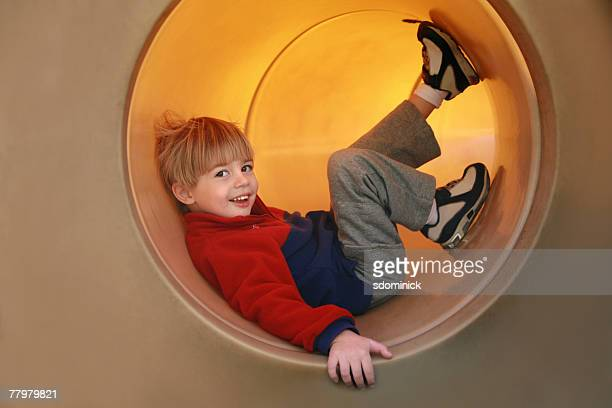 An almost 4 year old boy having fun in a park tunnel.