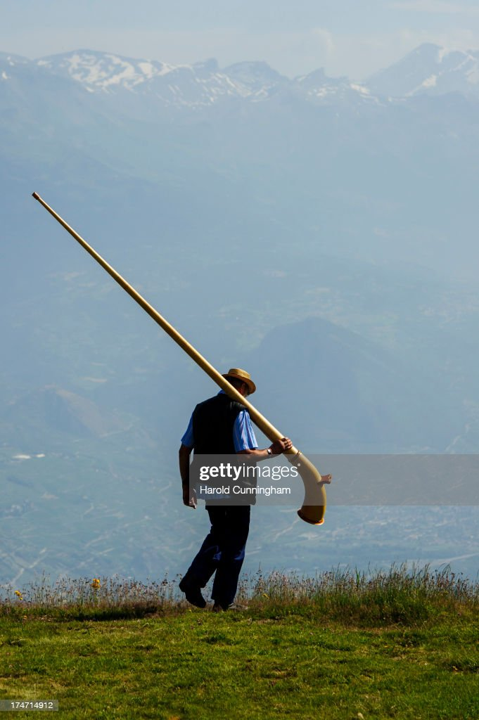An alphorn player walks in a grassland on July 28, 2013 in Nendaz, Switzerland. About 150 alphorn blowers performed together on the last day of the international Alphorn Festival of Nendaz. The Swiss folkloric wooden wind instrument was used in most mountainous regions of Europe by mountain dwellers as signal instruments.