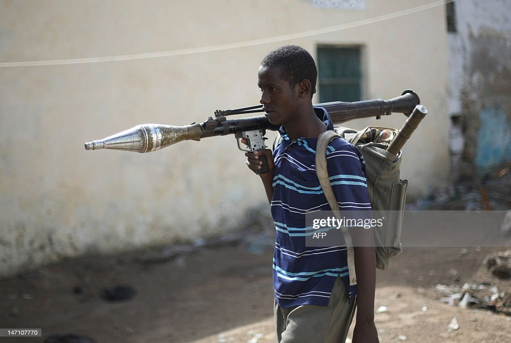 An AlShabab Islamic fighter wearing a rock launcher walk at a front line section in sanca district in Mogadishu on July 21 2009 Somalia's hard line...