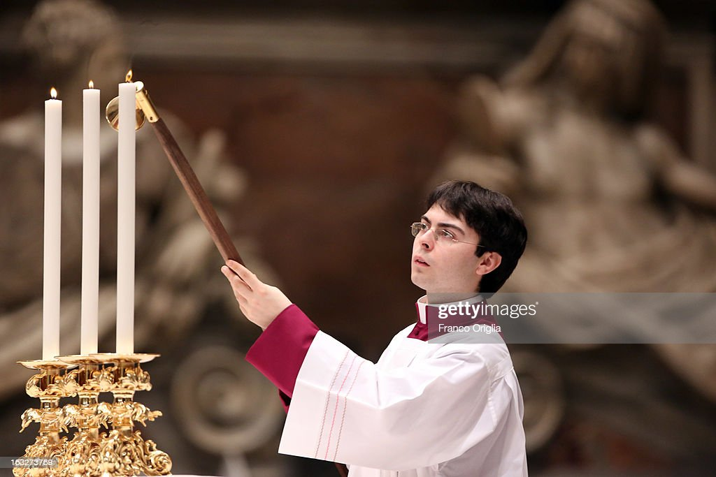 An altar boy lights candles in St. Peter's Basilica during a meeting of prayer at St. Peter's Basilica on March 6, 2013 in Vatican City, Vatican. The start-date of the conclave to elect a new Pope, following the resignation of Pope Benedict XVI, has yet to be confirmed as many cardinals have sought more time to discuss the issues currently facing the Catholic church.