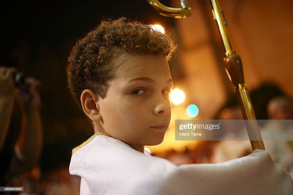 An altar boy looks on during Semana Santa (Holy Week) services in Paroquia Nossa Senhora da Paz on April 19, 2014 in Rio de Janeiro, Brazil. Holy Week marks the last week of Lent and the beginning of Easter celebrations for Catholics. Brazil holds more Catholics than any other country.