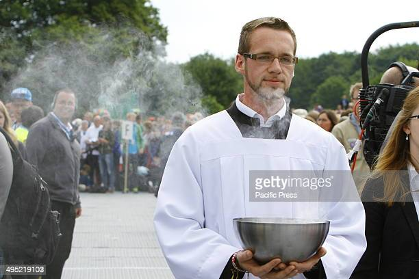 REGENSBURG BAVARIA GERMANY An altar server carries a bowl with burning incest from the altar to be used to incense the congregation at the closing...