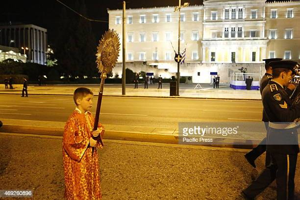 An altar server carries the ripidion past the Greek Parliament Thousands of people lined the street for this year's Good Friday's Epitaphios...