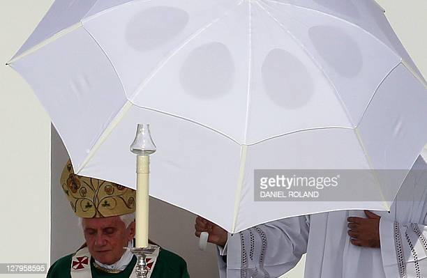 An altar server holds an umbrella to protect Pope Benedict XVI against the sun during a mass on the airfield in Freiburg southern Germany on...