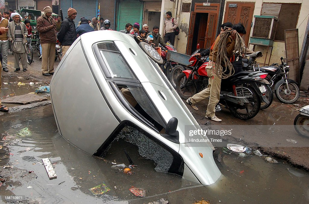 An Alto car fell inside a crater on road near busy market of Chopla on Thursday, December 27, 2012 in Ghaziabad, India. The car driver misjudged the depth of crater and hence fell straight into it. Local residents rescued the injured driver.