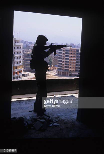An Amal militia man armed with an M16 automatic assault rifle stands aiming at a sniper position outside Bourj elBarajneh Palestinian refugee camp in...