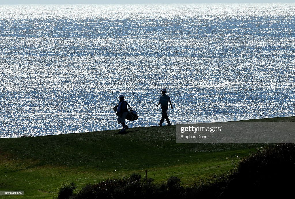 An amateur player and his caddie walk on the eighth fairway durng the first round of the Nature Valley First Tee Open at Pebble Beach at Pebble each Golf Links on September 27, 2013 in Pebble Beach, California.