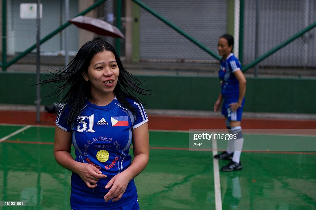 An amateur volleyball players talks to a friend during a game in heavy rains brought on by approaching Typhoon Usagi in Hong Kong on September 22, 2013. The team, made up of women from the Philippines who work as domestic helpers in Hong Kong, kept their usual Sunday volleyball practice time as the severe typhoon hit the territory. Severe Typhoon Usagi barrelled towards Hong Kong on September 22, shutting down one of the world's busiest sea ports and throwing flight schedules into disarray from Europe to the United States.