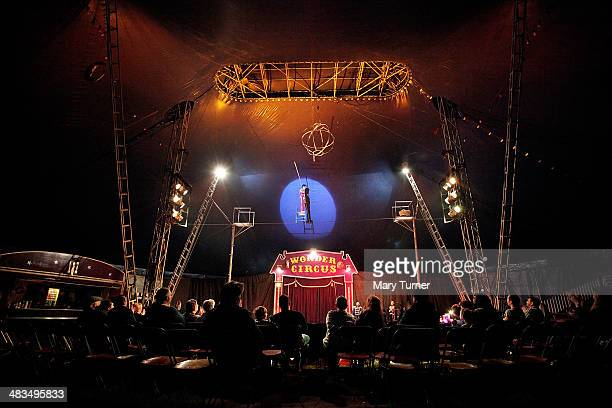 An amazed audience looks up to the roof of the big Top tent as high wire act Marco Polo balances on a chair on a wire high above the ground during Mr...