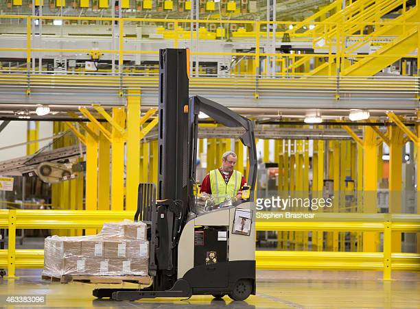 An Amazon Associate drives a forklift past conveyors at an Amazon Fulfillment Center on February 13 2015 in DuPont Washington The eighth generation...