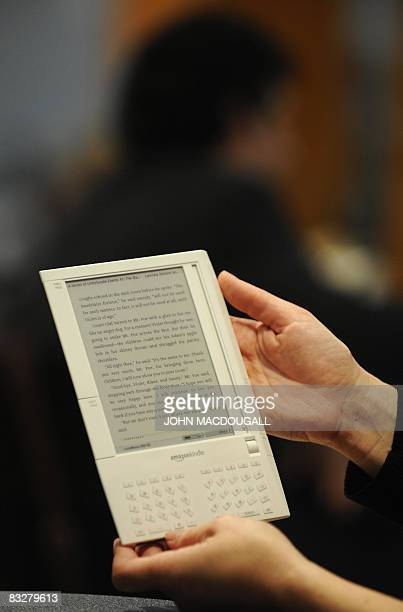An Amazon employee displays their new ereader device 'Kindle' at the Frankfurt Book Fair on October 15 2008 Turkey is guest of honour at the 60th...