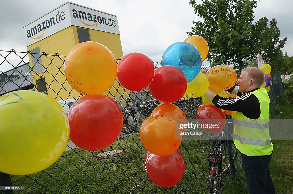 An Amazon worker fixes baloons with messages from striking workers written on them onto a fence during a strike outside the Amazon warehouse on May 14, 2013 in Leipzig, Germany. Approximately 5,000 Amazon workers at the Leipzig and Bad Hersfeld warehouses have gone on a 24-hour strike in an effort to press the company harder in their ongoing labour dispute over wages and work hours.
