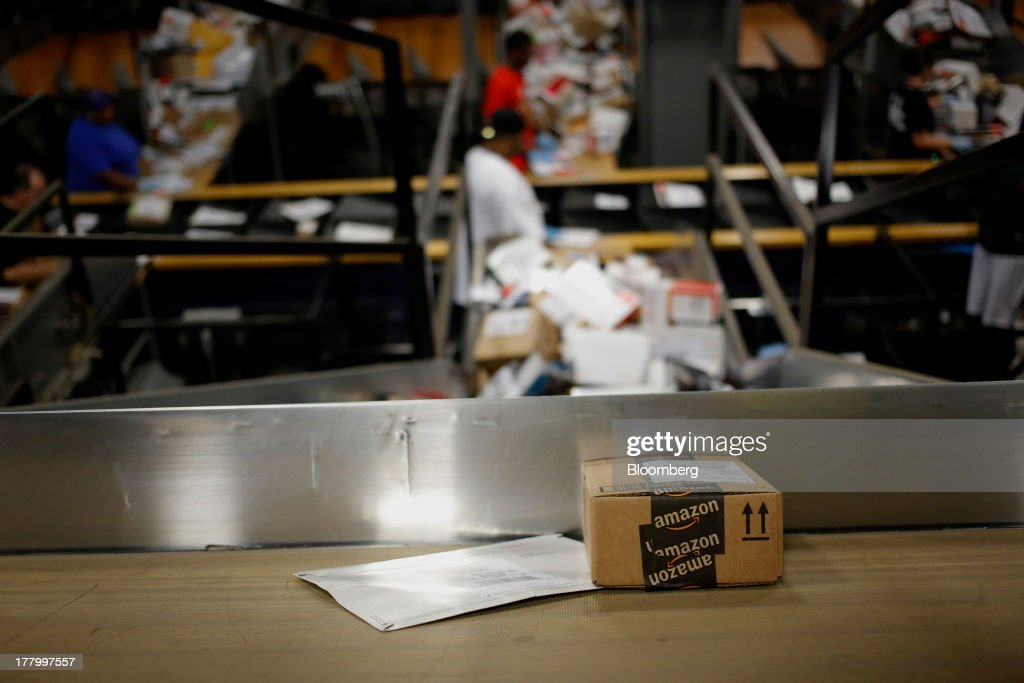 An Amazon.com box moves along a conveyor belt as automated systems sort packages during United Parcel Service Inc. (UPS) Worldport overnight shipping operations at Louisville International Airport in Louisville, Kentucky, U.S., on Thursday, Aug. 22, 2013. Founded 106 years ago as a bicycle messenger service, UPS now handles 16.3 million packages and documents per day and is considered an economic bellwether because of the diverse items it delivers such as industrial parts, health-care products and financial paperwork. Photographer: Luke Sharrett/Bloomberg via Getty Images
