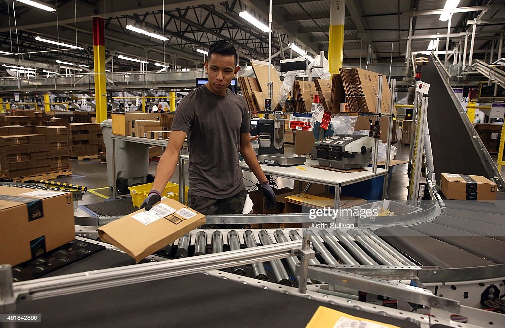 An Amazoncom worker sorts packages onto a conveyor belt at an Amazon fulfillment center on January 20 2015 in Tracy California Amazon officially...