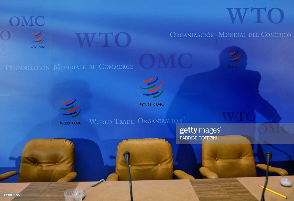 An Ambassador is seen in silhouette as he leaves a press conference during the trade talks at the World Trade Organisation headquarters on July 28...