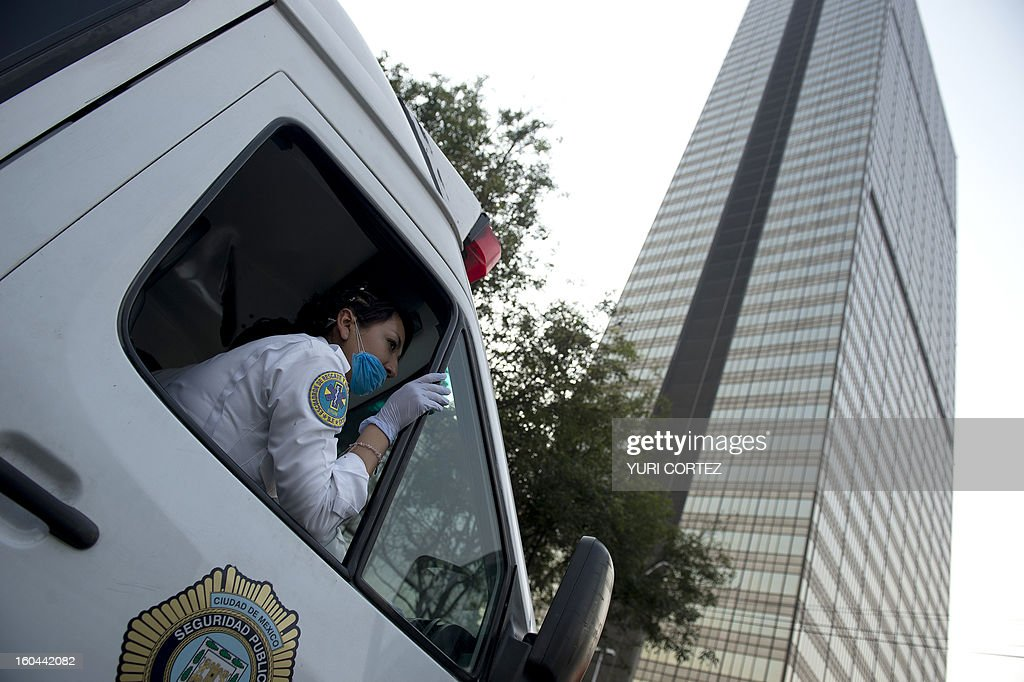 An ambulance arrives at the scene of the skyscraper ablaze that houses the headquarters of state-owned Mexican oil giant Pemex in Mexico City on January 31, 2013. An explosion rocked the skyscraper, leaving up to now 22 injured people, as a plume of black smoke billowed from the 54-floor tower. AFP PHOTO/Yuri CORTEZ