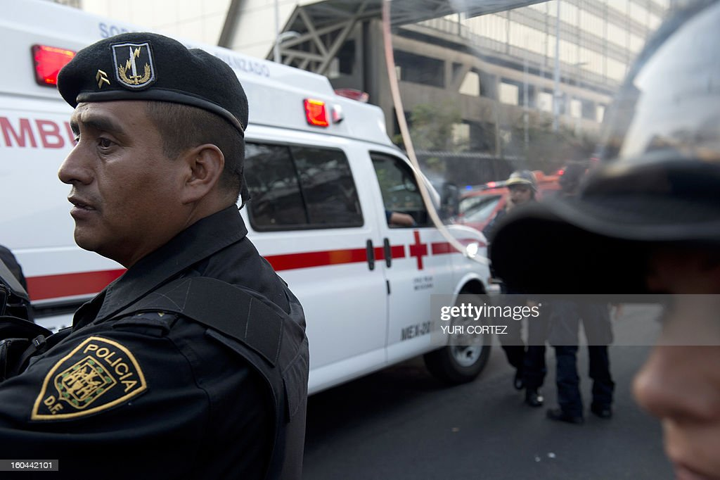 An ambulance arrives at the scene of the skyscraper that houses the headquarters of state-owned Mexican oil giant Pemex in Mexico City on January 31, 2013, following a blast inside the building. An explosion rocked the skyscraper, leaving up to now 14 dead and 40 injured, as a plume of black smoke billowed from the 54-floor tower, according to official sources. AFP PHOTO/Yuri CORTEZ