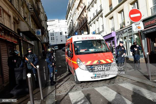 An ambulance car drives past French police patrolling near Rue de la Goutte d'Or in the north of Paris on January 7 after police shot a man dead as...