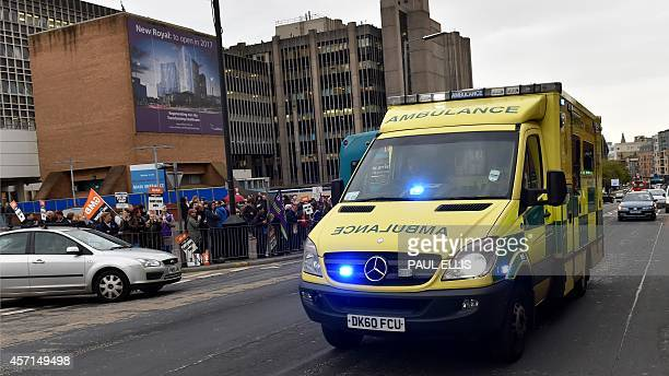 An ambulance carrying a member of the military and a paramedic drives past a protest at Royal Liverpool Hospital in Liverpool north west England on...
