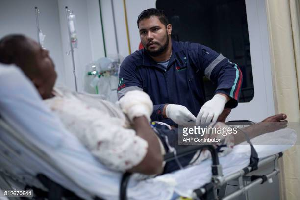 An ambulance driver prepares a patient who was beaten and shot in the hand to be transferred to the Miguel Couto hospital located 23 km away at...